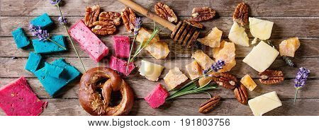 Variety of colorful holland cheese traditional soft, old, pink basil, blue lavender served with pecan nuts, honey, lavender flowers, pretzels bread over wooden planks background. Flat lay