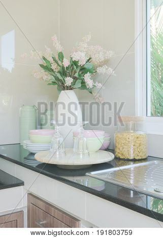 Ceramic Kitchenware And Flower Vase On Black Counter Top In The Kitchen