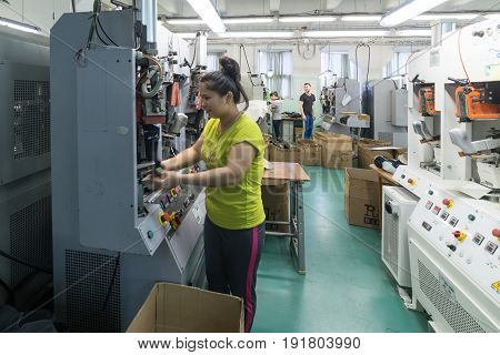 MOSCOW, RUSSIA - FEBRUARY 21, 2017: Moscow shoe factory JSC RALF RINGER. A female worker is working on a shoe forming machine.
