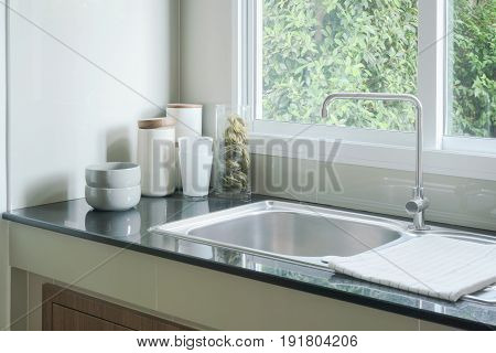 Kitchen Sink Next To Window And White Ceramicware On Counter Top