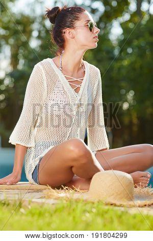 Young woman sun bathing in spa resort swiming pool