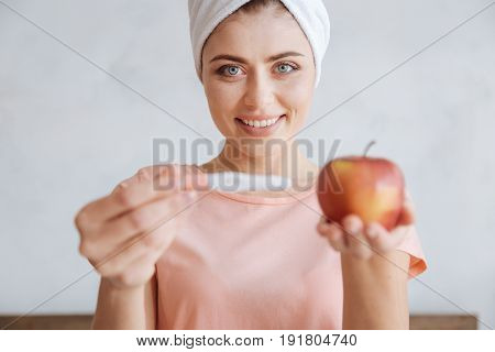 Cant believe it. Selective focus on a grey-eyed woman of an unearthly beauty smiling while holding a pregnancy test and a coxs apple.