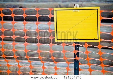 blank yellow sign on bright orange construction fence
