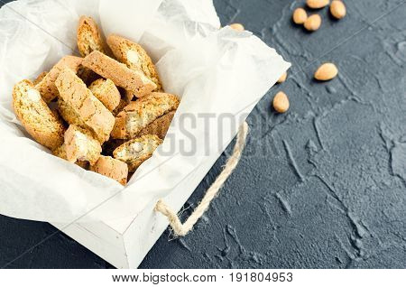 Traditional italian almond cookies cantuccini overhead view on black stone background. Homemade biscotti in a white wooden box on dark concrete table.