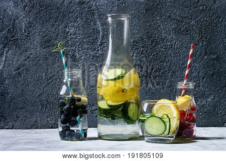 Citrus cucumber berries blueberry and raspberry sassy sassi water for detox in glass bottles on gray texture background. Clean eating, healthy lifestyle concept, sunlight