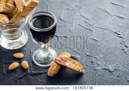 Traditional italian almond cookies cantuccini with glass of red wine on black stone background with space for text. Homemade biscotti on dark concrete table. Copy space.
