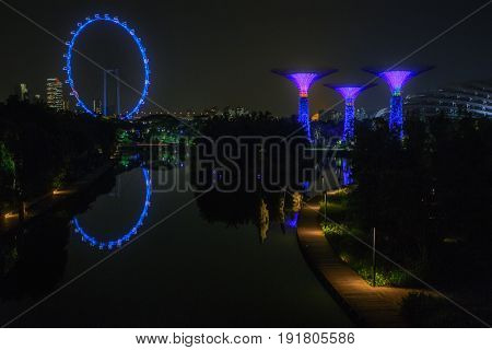Singapore - July 01, 2015: Singapore city skyline and view of Marina Bay  Gardens by the Bay at night in Singapore city. SuperTree Grove under Blue Night Sky in Singapore