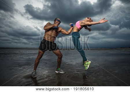 Beautiful sport couple, strong boxer with dumbbells practicing with his girl at sunset
