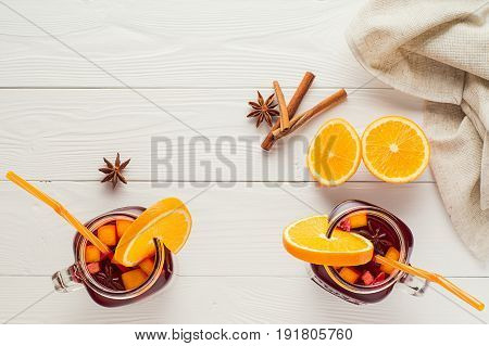 Two fruit tea in vintage glass jars with drinking straw on white wooden background top view. Vintage mason jars with ice hibiscus tea orange cinnamon and star anise on white table flat lay.