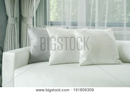 Pillows Lay On White Sofa With Sheer Curtain In Background