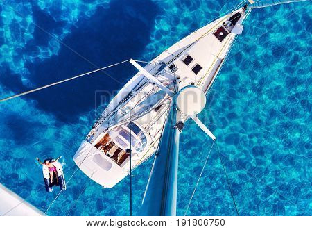 Formentera Spain - June 10 2017: Person relaxing on a inflatable boat yacht and clear Mediterranean sea view from the mast. Formentera. Balearic Islands. Spain