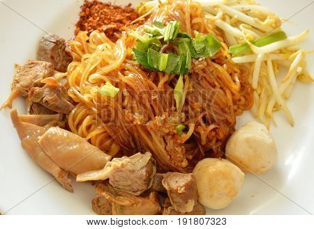 dried thin rice noodle topping braised pork dressing cayenne pepper on dish
