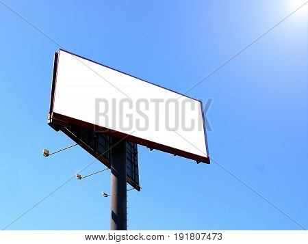 Wide white background with backlighting large empty billboard, against the blue sky, lit by the sun, for text