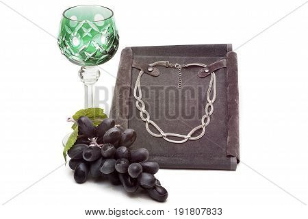 Silver chain glass glass and a bunch of grapes on a white background