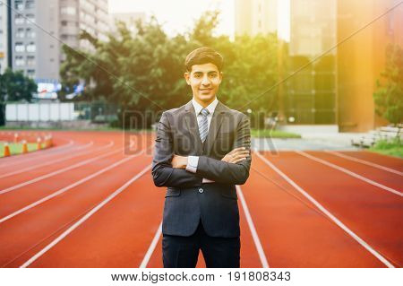 Smiling Happy And Confident Business Executive Standing With Arms Folded In Performance Race Track B