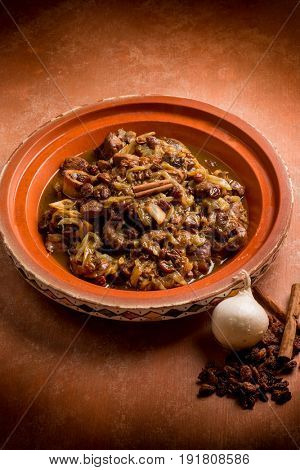 open tajine with meat, onion, dried grape and cinnamon