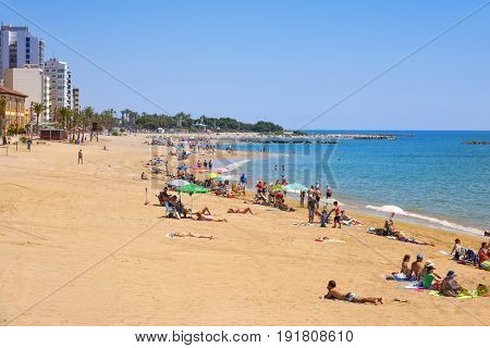 VINAROS, SPAIN - JUNE 12, 2017: People enjoying the warm weather at Playa del Forti beach in Vinaros, in the Costa del Azahar, Spain