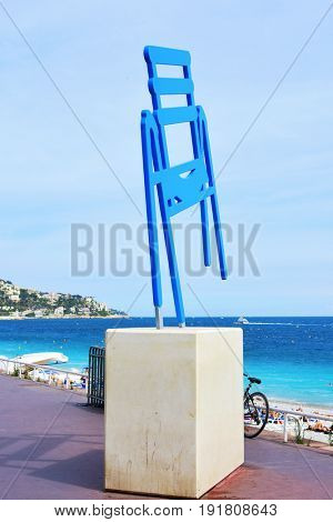 NICE, FRANCE - JUNE 4, 2017: A sculpture depicting the characteristic blue chairs at the famous Promenade des Anglais in Nice, in the French Riviera, France