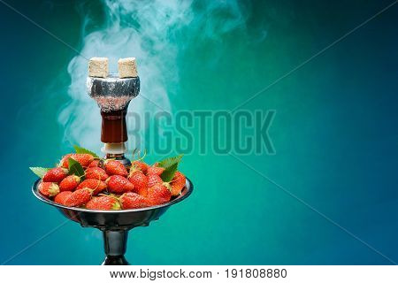 Smoking hookah with fruit head on blue background
