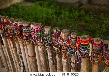 Colored bracelets dedicated to the victims of the killing fields of Choeung Ek in Phnom Penh, Cambodia. Selective focus