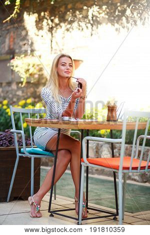 Young dreamy woman sits at a table of summer cafe