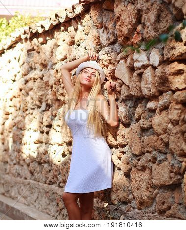 Young dreamy woman on streets of old tourist town enjoy the sunlight