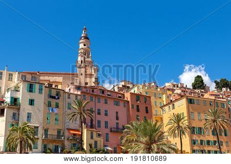 Bell tower among old colorful houses of Menton under blue sky on French Riviera.