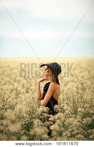 Young woman in black dress and hat among flowering meadow. She looks away thoughtfully.
