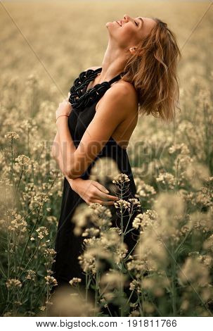 Happy young woman in black dress among flowering meadow. She is very joyful cheerful and laughs.