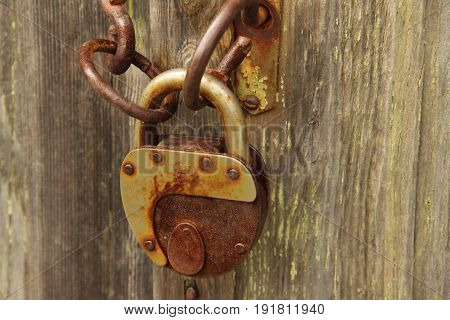 Old grunge rusty padlock on wooden background.