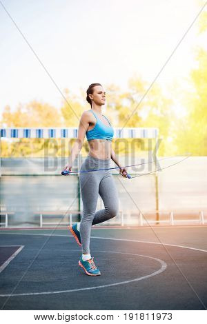 Full Length View Of Young Serious Sportswoman Exercising With Skipping Rope On Stadium