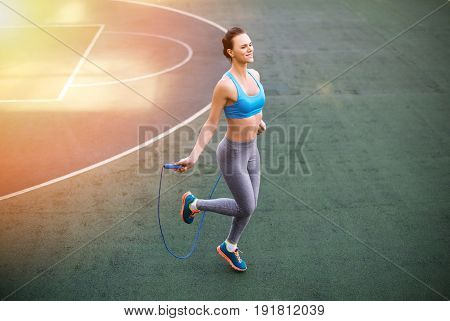High Angle View Of Young Smiling Woman In Sportswear Training With Skipping Rope