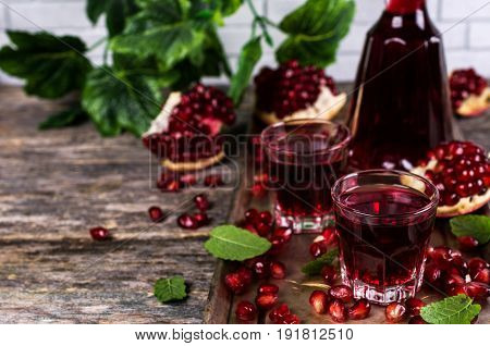 Transparent burgundy drink with pomegranate seeds and mint. Selective focus.