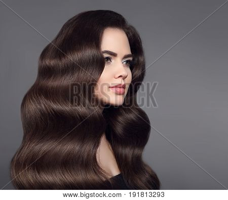 Healthy hair. Brunette girl portrait with long shiny wavy hair. Beautiful model with curly hairstyle and makeup isolated on studio dark background. Shampoo care product.