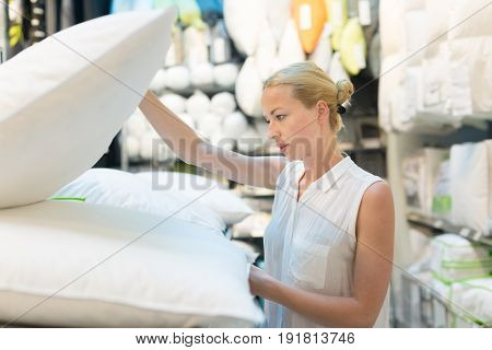 Pretty, young woman choosing the right item for her apartment in a modern home decor furnishings store. Shopping in retail store.