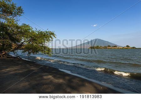 Beach in the Ometepe Island in Lake Nicaragua with a volcano on the background in Nicaragua; Concept for travel in Nicaragua and Central America