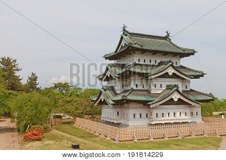 HIROSAKI JAPAN - MAY 23 2017: Main keep (donjon) of Hirosaki Castle with Mount Iwaki on the background. Was erected by Tsugaru Nobuhira in 1611 reconstructed in 1810 Important Cultural Property
