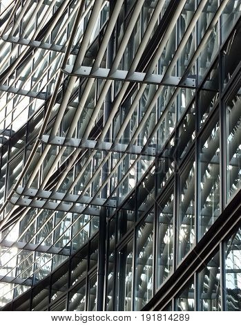 facade of modern high-tech glass and steel building with reflective windows and metal framework
