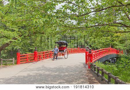 HIROSAKI JAPAN - MAY 23 2017: Rickshaw-puller on Sugi-no-ohashi Bridge of Hirosaki Castle Japan. Castle was erected by Tsugaru Nobuhira in 1611 designated National Historic Site in 1952