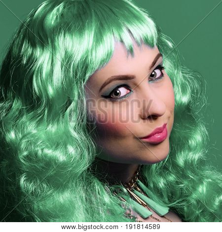 Young woman with green colored wig on green background.
