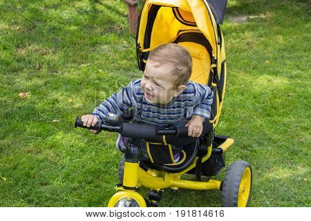 crying little boy on a tricycle on the grass