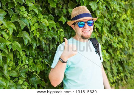 Young hipster man with thumb up in park
