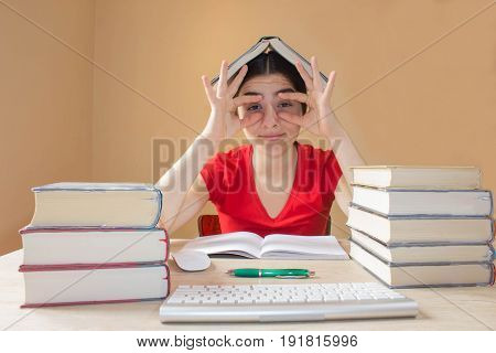 Young Girl student with pile of books and notes studying indoors. Education concept