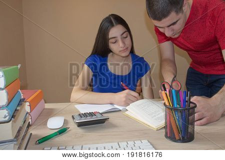 Older brother explaining exercise Student sister Working At Desk with writing lesson