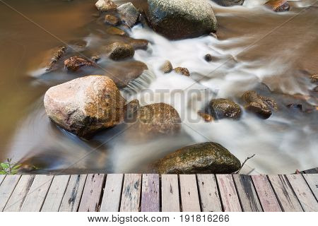Scenery of brown watercourse with flowing water and white wave on rock river near by wooden bridge.
