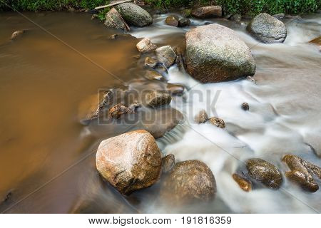 Scenery of brown watercourse with flowing water and white wave on rock river.