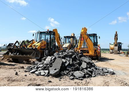 Large yellow excavators, diggers on construction site