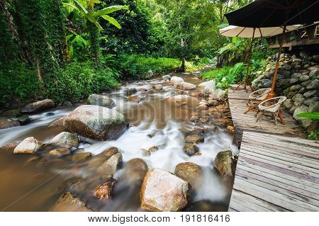 Scenery of flowing water of rock river inside forest area of Thailand which having small relax place nearby.