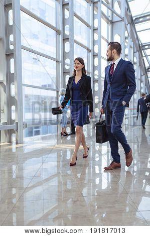 Business people walking in modern glass office corridor