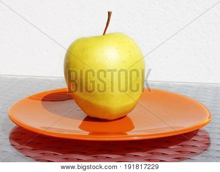 Closeup view of yellow ripe apple with water drops on a orange plate.